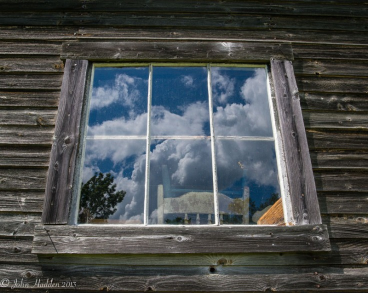 Fair weather cumulus clouds reflect in a weathered window.