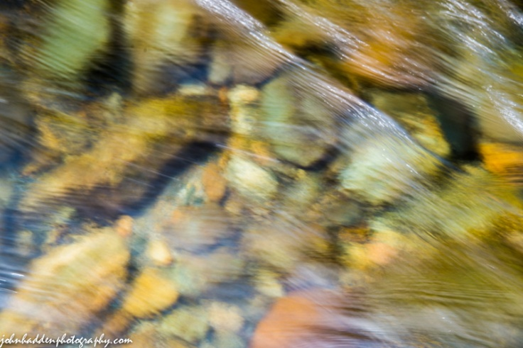 Flowing water blurs river bottom stones in the Huntington River